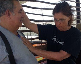 Susan shown healing a sick workman at his business