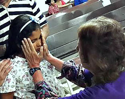 photo of a woman laying hands on a blind girl, who immediately had her sight restored