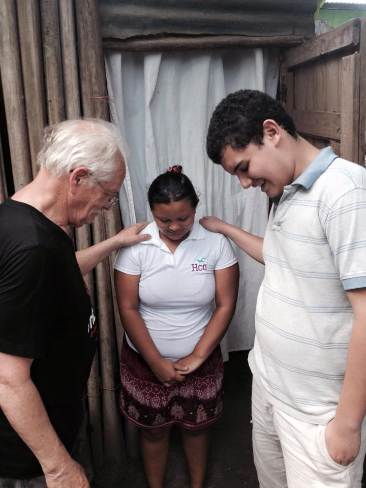 Elderly man and a boy giving healing prayer to a woman